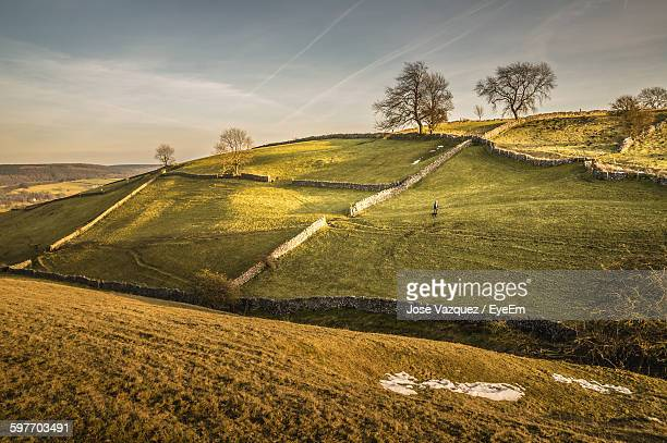 person walking on field with stone wall against sky - stone wall stock pictures, royalty-free photos & images