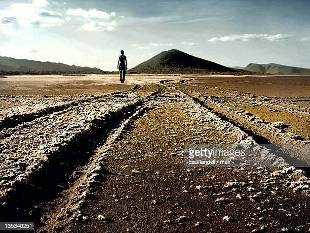Person walking on road in desert