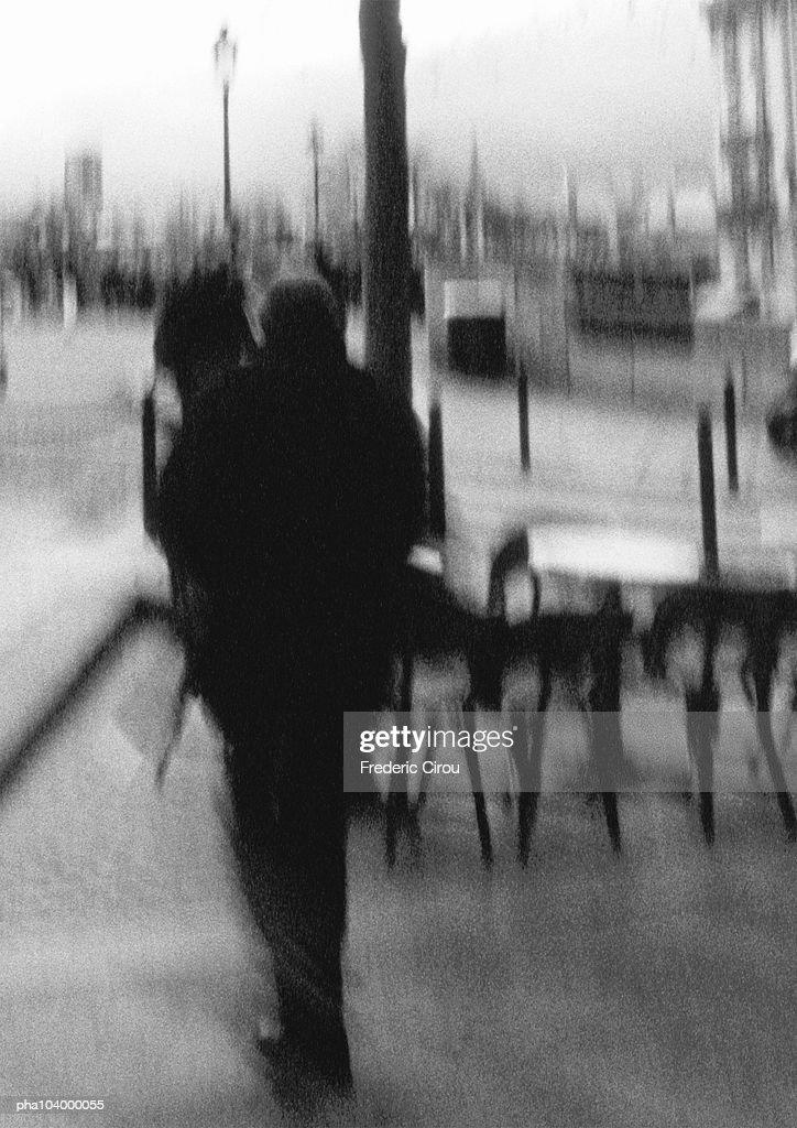 Person walking on sidewalk, blurred, b&w : Stockfoto