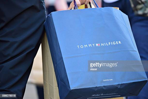 person walking on sidewalk with tommy hilfiger shopping bag - tommy hilfiger designer label stock pictures, royalty-free photos & images
