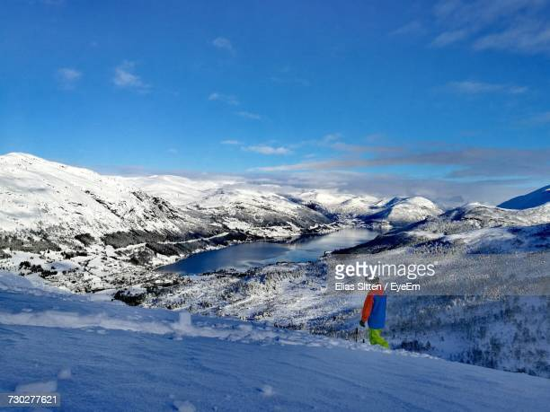 Person Walking On Snowy Mountain Against Blue Sky During Winter