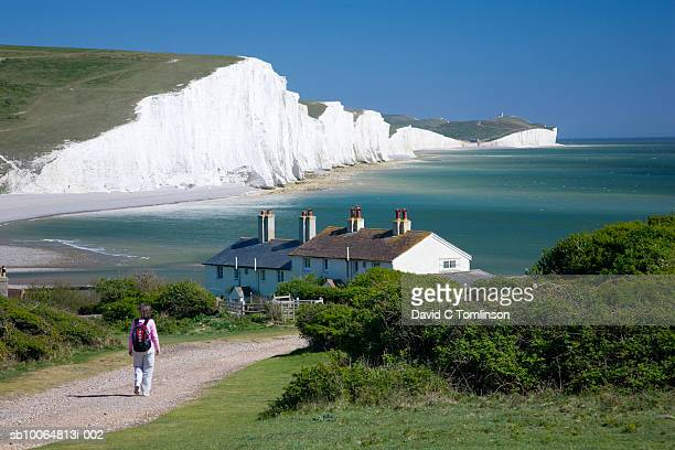 Person walking towards houses and the Seven Sisters cliffs, Seaford Head, Sussex, England, UK