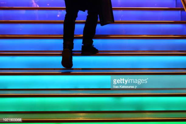 person walking up colorful staircase - steps stock photos and pictures