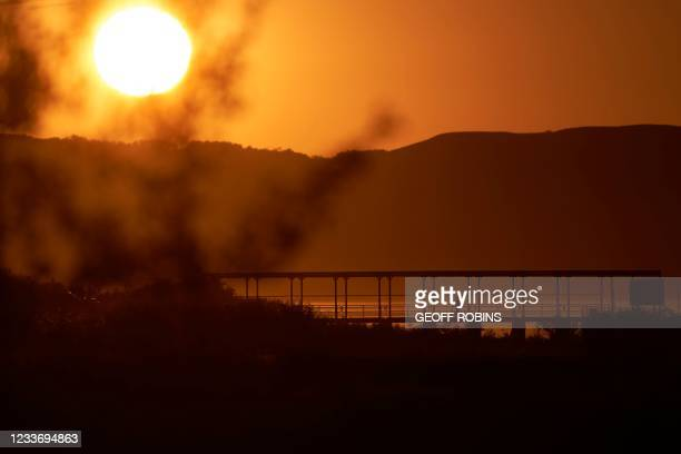 Person walks across a bridge on the Cowessess First Nation in Saskatchewan as the sun sets over Crooked Lake on June 27, 2021. - Fires on Saturday...