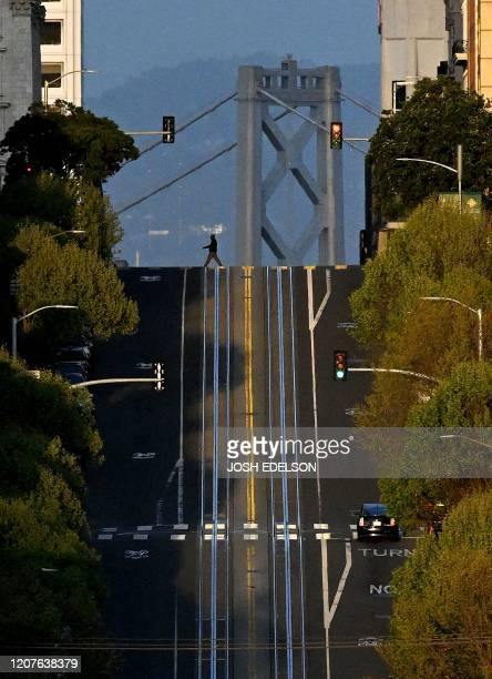 TOPSHOT A person walks across a mostly empty California Street in San Francisco California on March 18 2020 San Francisco along with seven other Bay...