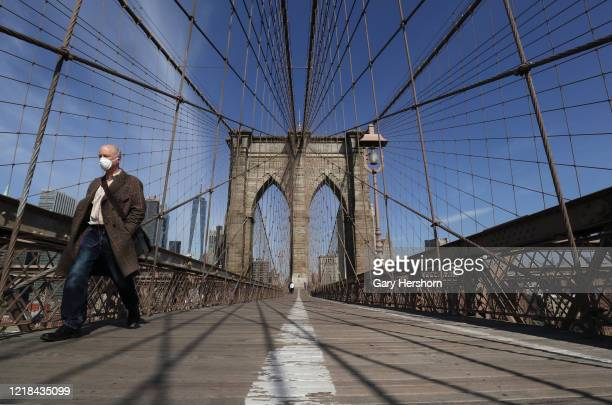 A person walks across the Brooklyn Bridge on Easter Sunday on April 12 2020 in New York City