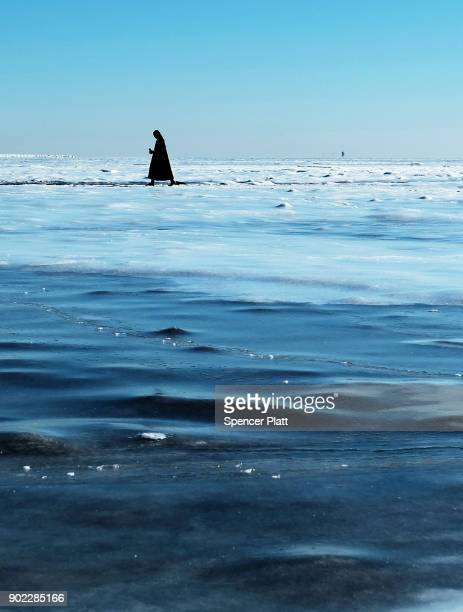 A person walks along a frozen section of Long Island Sound as temperatures continue to stay below freezing in much of the Northeast on January 7 2018...