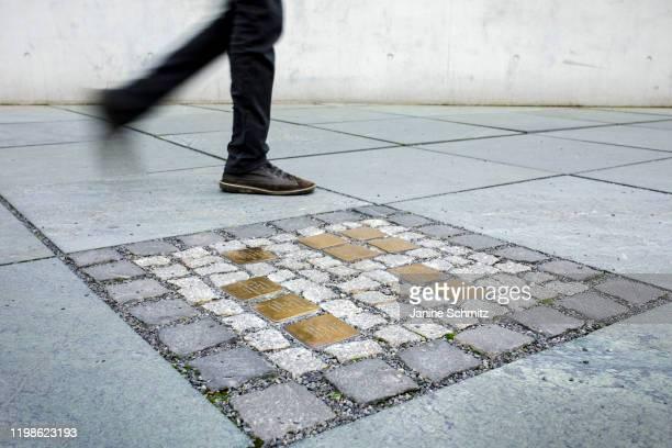 Person walks along Stolpersteine or stumbling blocks on a side walk on February 04, 2020 in Berlin, Germany.