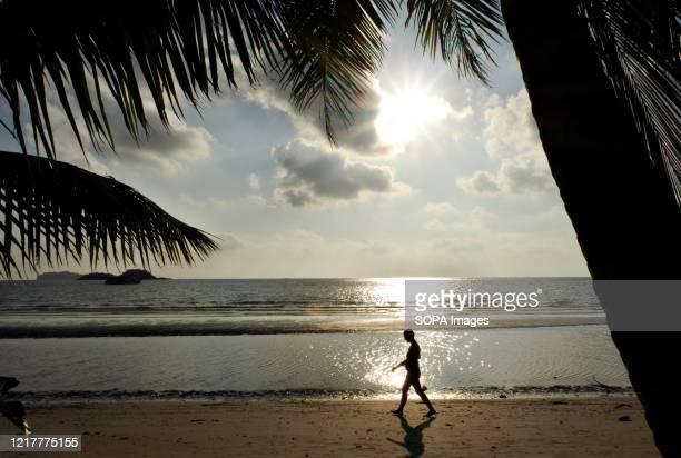 Person walks along the beach on Koh Chang Island in Trat province, 350 kms south of Bangkok during sunset.