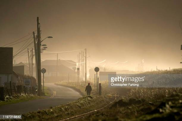 A person walks along the sea defences in the Welsh village of Fairbourne in Gwynedd which is under threat from climate change and rising seas causing...