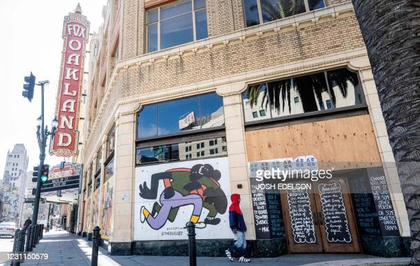 Person walks by a boarded-up shop in Oakland, California on February 12, 2021. - Racial minorities have borne the brunt of the Covid-19 pandemic in...