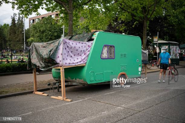 """Person walks by a camping trailer in the so-called """"Capitol Hill Autonomous Zone"""" on June 10, 2020 in Seattle, Washington. The zone includes the..."""