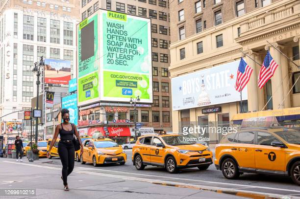 A person walks by a CDC billboard reminding people to wash hands outside Madison Square Garden as the city continues Phase 4 of reopening following...