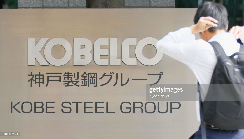 A person walks by a logo of Kobelco, Kobe Steel Ltd 's brand