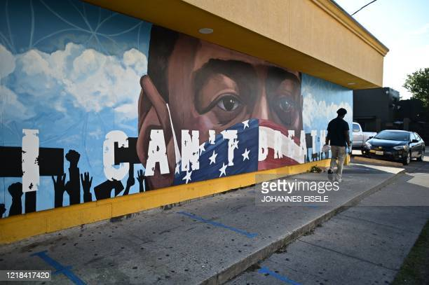 A person walks by a mural for George Floyd in Houston Texas on June 82020 Democrats vowed June 7 2020 to press legislation to fight systemic racism...