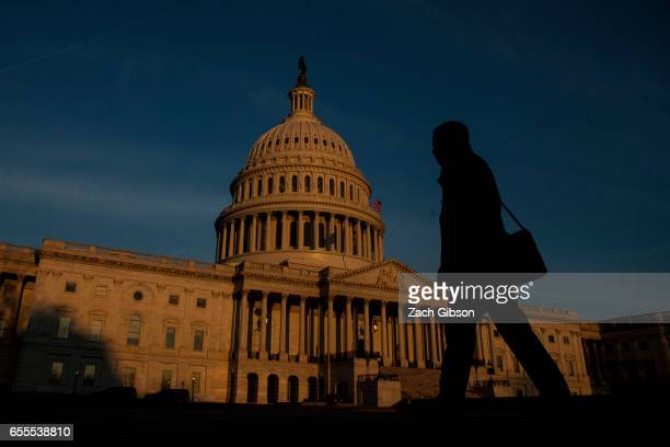 A person walks by as the sun rises near The United States Capitol Building on March 20 2017 in Washington DC The Senate will hold a confirmation...