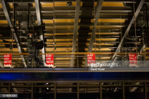 Person walks by Black Lives Matter signs inside Seattle City Hall after demonstrators marched inside led by Seattle City Council member Kshama Sawant...