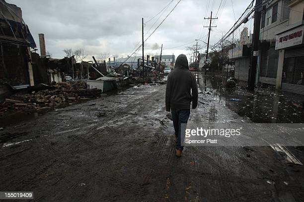 Person walks by homes and businesses destroyed during Hurricane Sandy on October 30, 2012 in the Rockaway section of the Queens borough of New York...