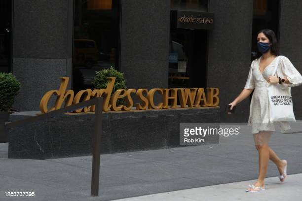 A person walks by the Charles Schwab logo in midtown as New York City moves into Phase 2 of reopening following restrictions imposed to curb the...