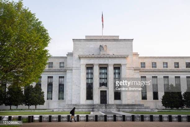 Person walks by the Federal Reserve on Saturday, April 25, 2020.