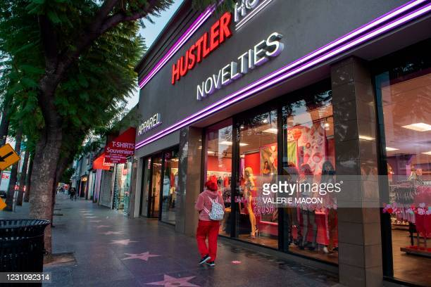 Person walks by the Hustler Hollywood store on February 10, 2021 in Hollywood, California. - US porn mogul Larry Flynt, best known as the publisher...