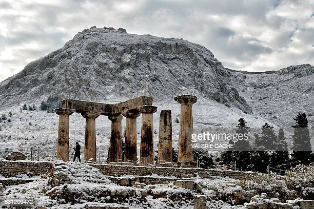 A person walks by the snowcovered temple of Apollon in Ancient Corinth on January 8 2017 Greece experiences rare cold wave with low temperatures and...