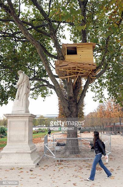 """Person walks by """"Tree Huts"""" a work by Japanese Tadaschi Kawamata on October 16, 2008 at the Tuileries garden in Paris during the preparations of the..."""