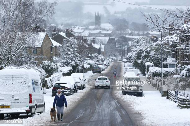 Person walks his dog on a snowy morning. Heavy snow fell overnight in West Yorkshire, causing dangerous driving conditions.