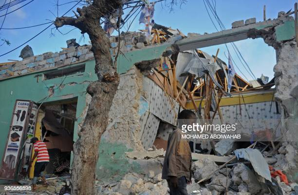 A person walks in front of a building destroyed by the explosion of the car bombing attack on a street in Mogadishu Somalia on March 22 2018 At least...