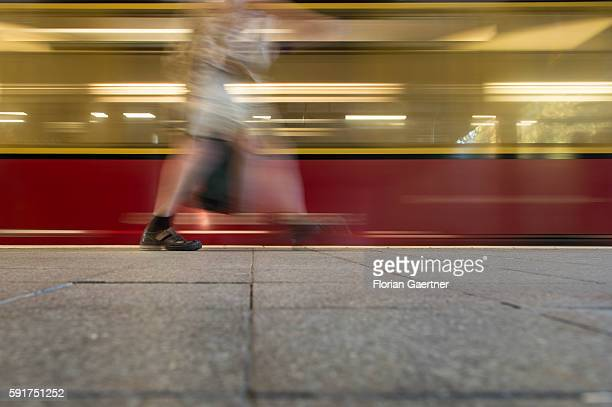 A person walks in front of the arriving city train on August 17 2016 in Berlin Germany