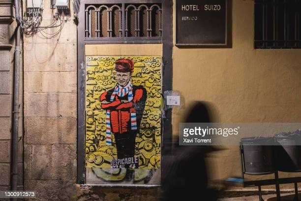 Person walks in front of the new work of the italian artist TVboy 'Despicable Me 4' featuring Vladimir Putin on February 07, 2021 in Barcelona,...