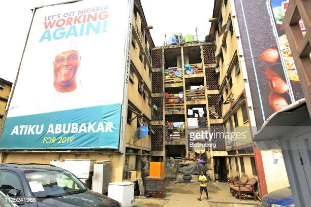 A person walks near a large poster for Atiku Abubakar candidate of the main opposition People's Democratic Party in Lagos Nigeria Saturday Feb 16...
