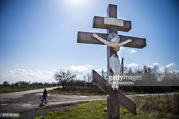 A person walks next to a crucifix partially destroyed by a shrapnel on a road on April 23 2015 near the site where the bulk of the Malaysian Airlines...
