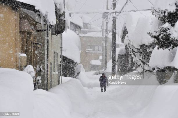 A person walks on a street deeply covered in snow in Fukui Japan on Feb 6 as heavy snow continued to fall on the Sea of Japan coast ==Kyodo