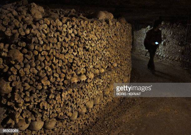 A person walks on April 3 2010 next to a wall made of skulls and bones at the Catacombs of Paris These subterrainian quarries had been used to store...