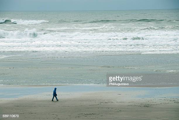 Person walks on beach along Pacific Ocean in Oregon