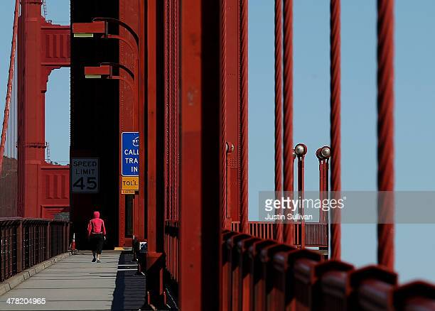 A person walks on the Golden Gate Bridge on March 12 2014 in San Francisco California A long debated suicide barrier on the Golden Gate Bridge could...