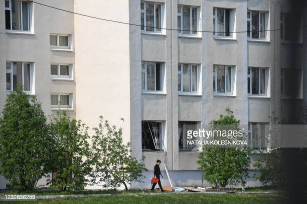 Person walks on the grounds of School No. 175 the morning after the shooting in Kazan on May 12, 2021. - At least nine people, most of them children,...