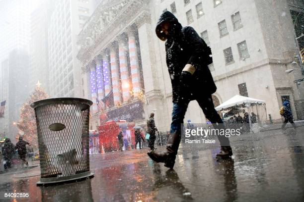 Person walks on Wall Street near the New York Stock Exchange during a during a snow storm December 19, 2008 in New York City. Stocks rose in early...