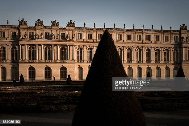 A person walks outside the Chateau de Versailles during a cold but sunny winter day in Versailles near Paris on January 6 2017 / AFP / PHILIPPE LOPEZ