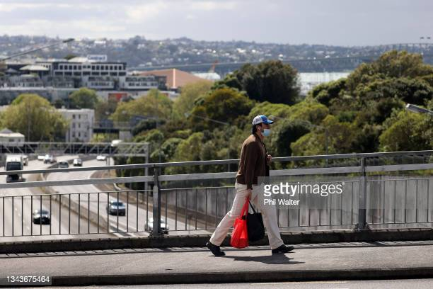 Person walks over the Auckland Southern motorway on September 29, 2021 in Auckland, New Zealand. 45 new COVID-19 cases have been recorded in New...