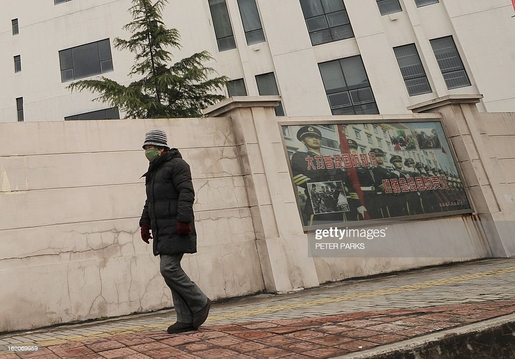 A person walks past a 12-storey building alleged in a report on February 19, 2013 by the Internet security firm Mandiant as the home of a Chinese military-led hacking group after the firm reportedly traced a host of cyberattacks to the building in Shanghai's northern suburb of Gaoqiao. Mandiant said its hundreds of investigations showed that groups hacking into US newspapers, government agencies, and companies 'are based primarily in China and that the Chinese government is aware of them.' AFP PHOTO / Peter PARKS