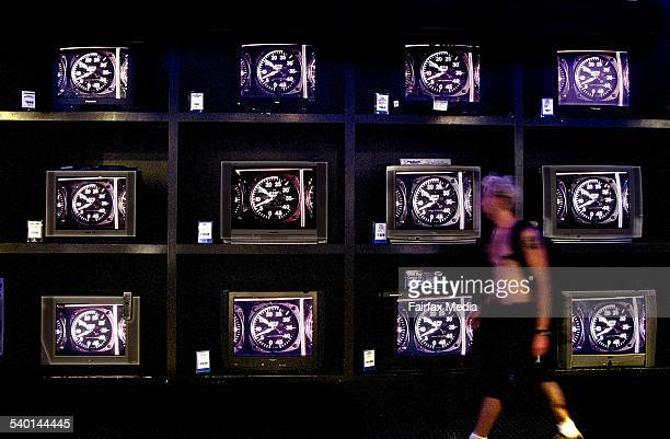A person walks past a bank of televisions on display with clocks on them 22 January 2001 AFR Picture by TANYA LAKE