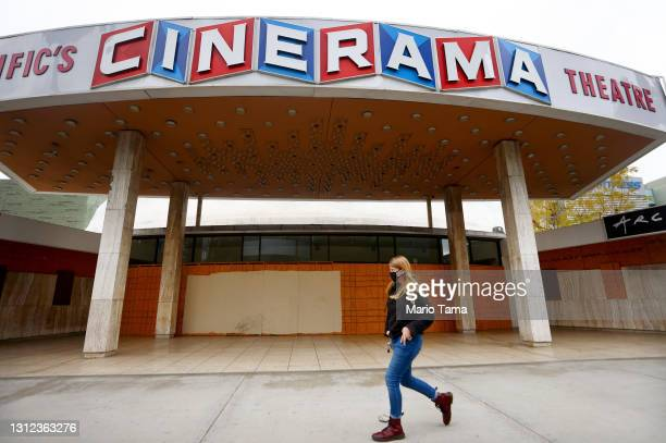 Person walks past a boarded up entrance at the famed Cinerama Dome at the shuttered ArcLight Hollywood movie theater on April 13, 2021 in Los...