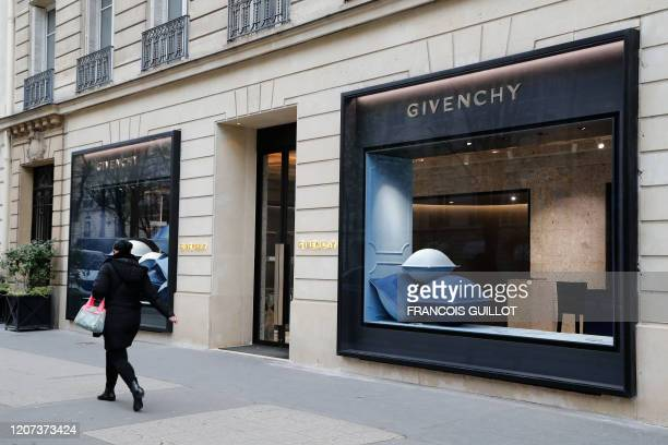 Person walks past a Givenchy shop closed due to the spread of the novel coronavirus on March 19, 2020 in Paris. - The French president is due to...