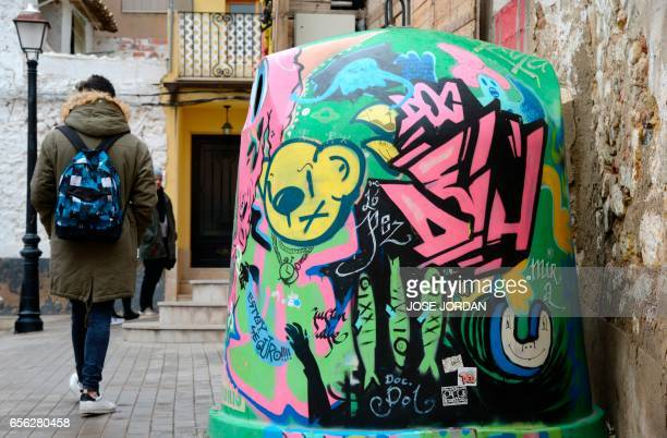 Person walks past a graffiti on a recycling can in Fanzara near Castellon de la Plana, on December 15, 2016. Fanzara, a Spanish hamlet in the...