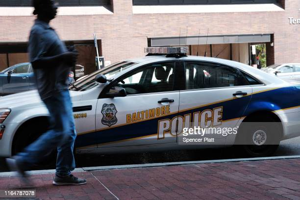 A person walks past a police car on July 28 2019 in Baltimore Maryland President Donald Trump has recently drawn criticism by calling the city of...
