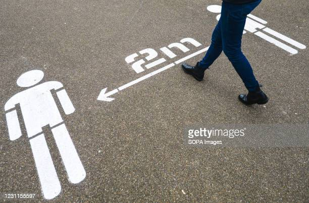 Person walks past a social distancing sign painted on the ground during the Level 5 Covid-19 restrictions. The Department of Health reported on...