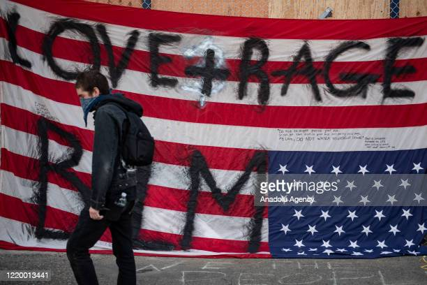 Person walks past an upside down American flag inside the âCapitol Hill Organized Protestâ formerly known as the âCapitol Hill Autonomous Zoneâ in...