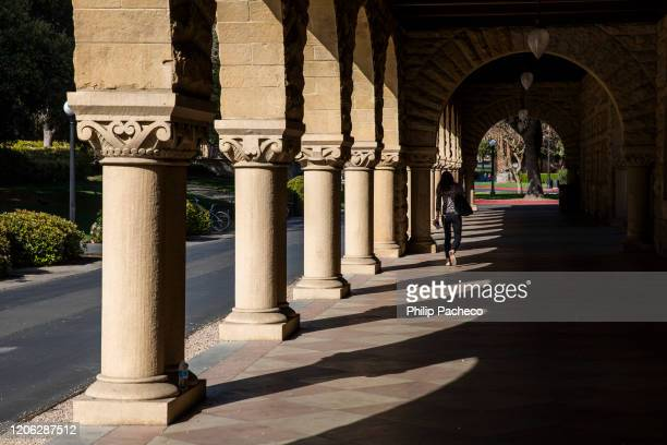 Person walks past archways during a quiet morning at Stanford University on March 9, 2020 in Stanford, California. Stanford University announced that...